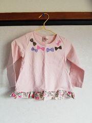 うすピンクにすそ柄物えりにリボンの長袖Tシャツ90